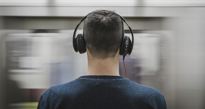 male worker wears headphones - 1200×630